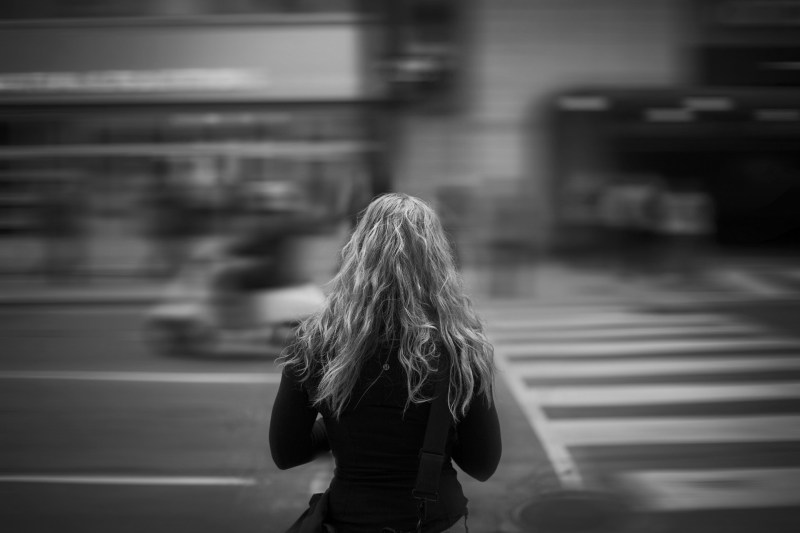 Woman standing in front of busy street