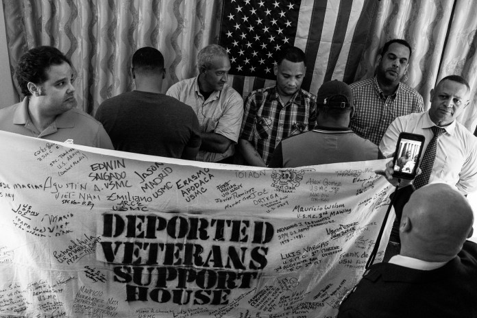 Left to right: Deported U.S. Marine Corps veteran Juan Goico, 39; deported unidentified U.S. Marine Corps veteran; deported U.S. Army veteran Jose Marquez; deported U.S. Army veteran Felix Portorreal, 42; deported unidentified U.S. Army veteran, 33; deported U.S. Army veteran Juan Alberto Garcia Santos, 46; and deported U.S. Navy veteran Manuel Estévez Rondon, 53; gather for the first time inside a hotel room during a live Facebook video by repatriated U.S. Army veteran Hector Barajas-Varela, 41, in Santo Domingo, Dominican Republic, Saturday, June 23, 2018.    The two unidentified veterans chose to remain anonymous because of stigmas against deportees living in the Dominican Republic. According to both veterans, being a deportee in the country can cost a person their job and can make them vulnerable to extortion by authorities. (Photo by Joel Angel Juárez/GroundTruth)