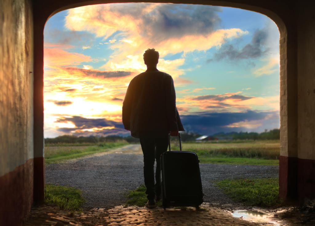man with suitcase staring out at sunset