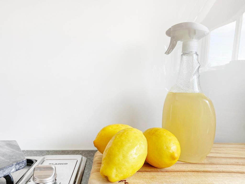 lemons and a spray bottle of yellow homemade cleaner