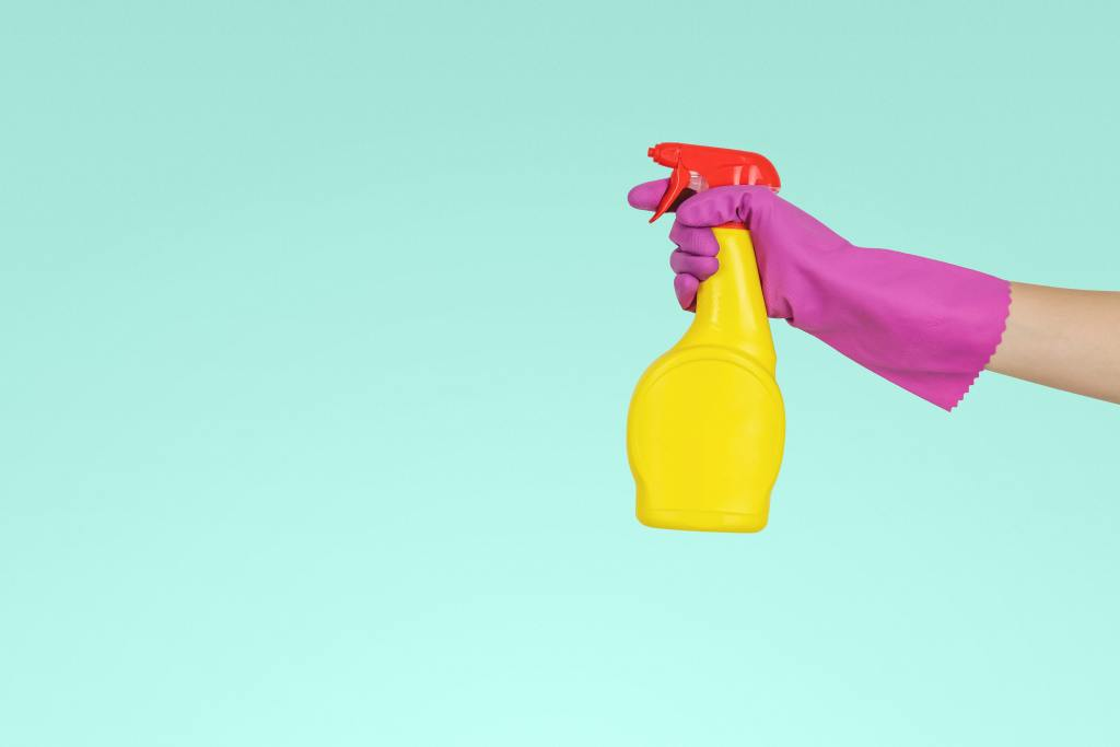 spray bottle held by a gloved hand against a green background