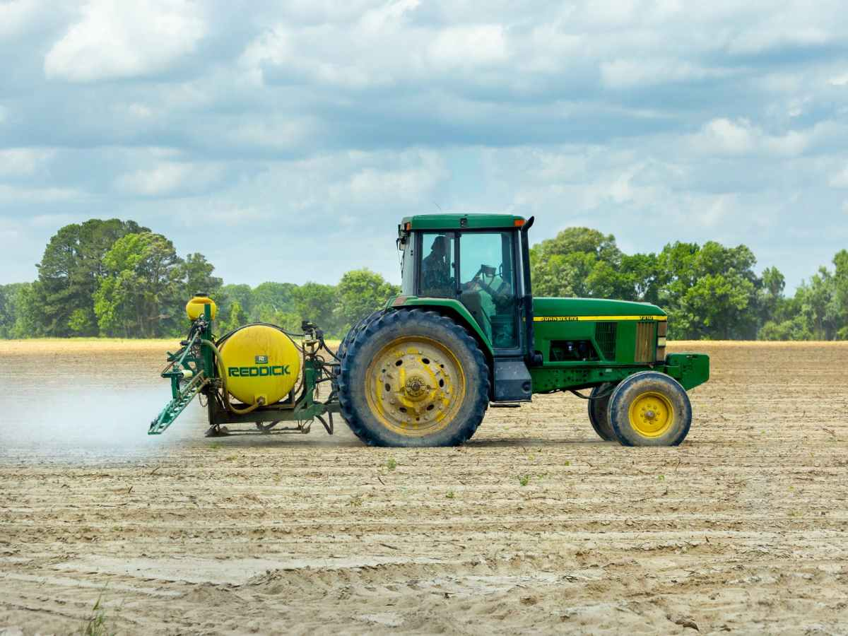 green and yellow tractor on large dirt field for monocropping