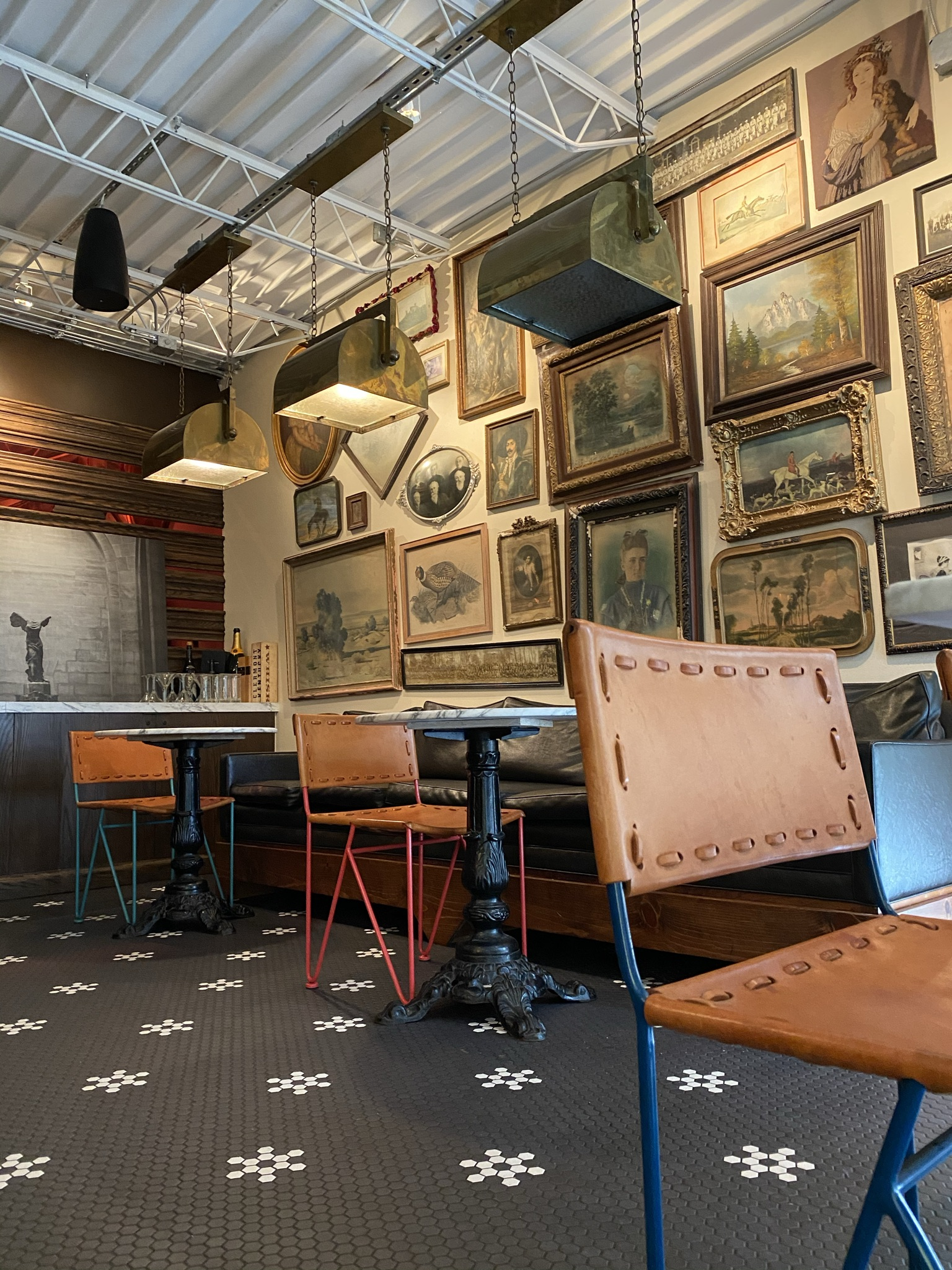 leather chairs and antique gold frames of old photos in the bar room of Ludivine