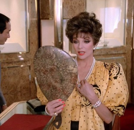 Joan Collins as Alexis looking into a mirror