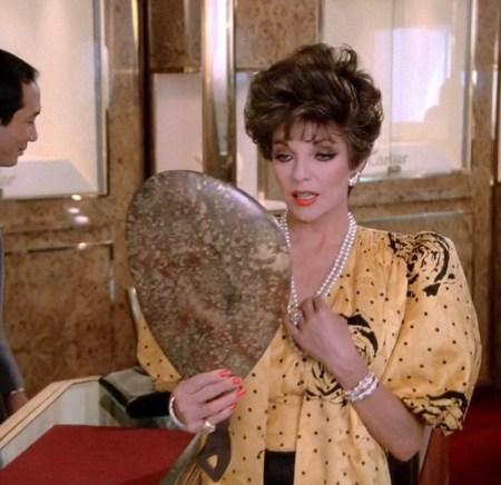 Joan Collins as Alexis looking into a mirror