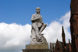 A statue of Robert Burns against a blue sky with fully clouds