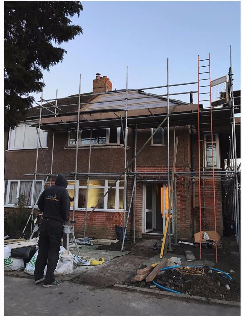 man in front of house covered in scaffolding