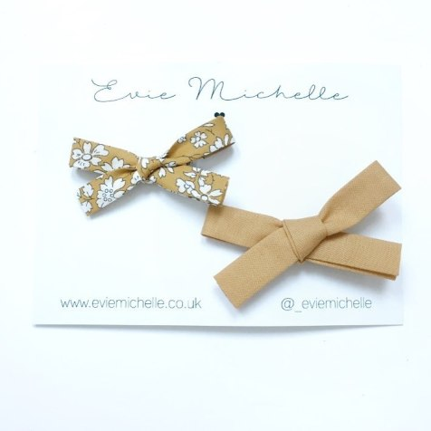 two girls mustard bows on white packaging