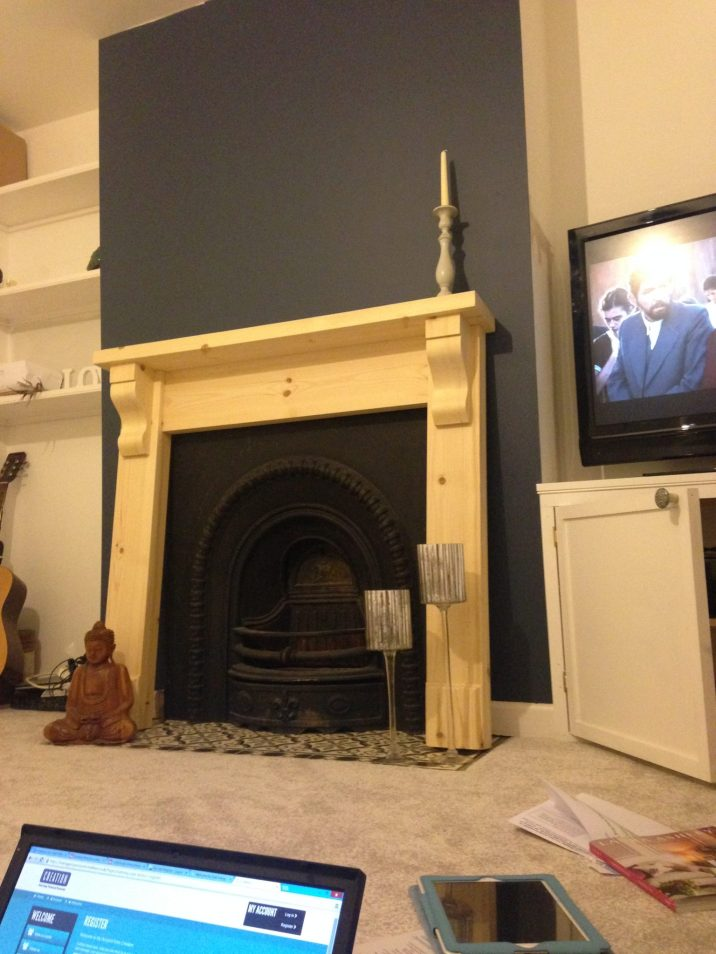 pine fire surround waiting to be attached to blue wall