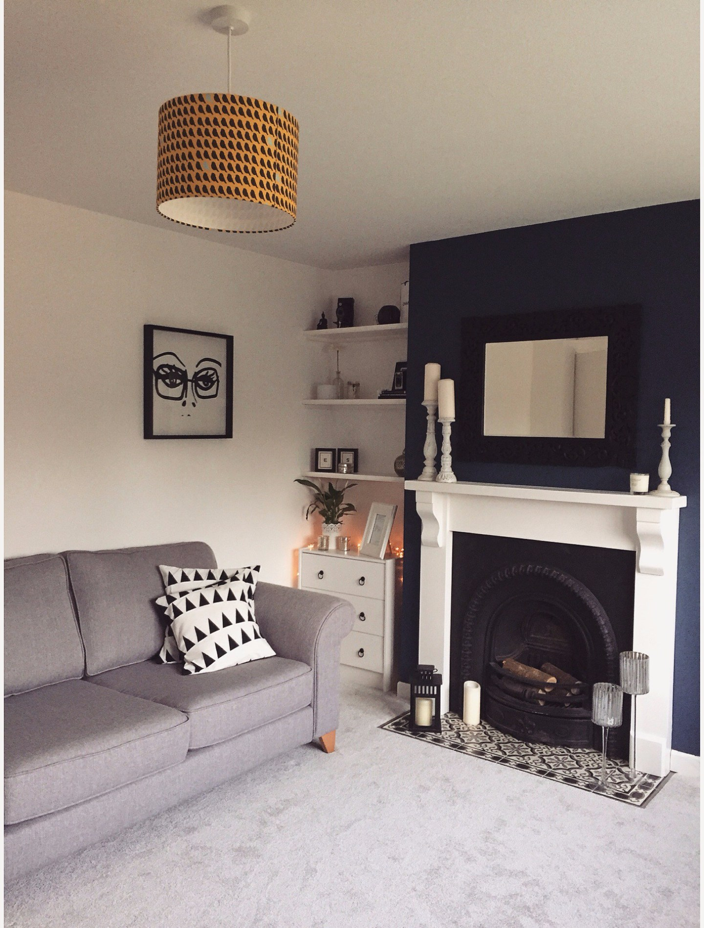 a modern living room with grey carpet and sofa, blue chimney breast, white fire surround and yellow lampshade