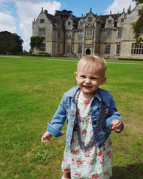 one year old girl standing in front of manor house in background with necklace around neck