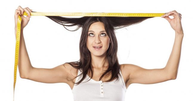 image of lady holding a tape measure above her head measuring the length of her hair