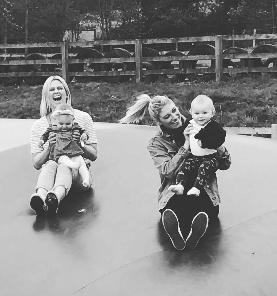two mothers and children laughing on bouncey pillow black and white image