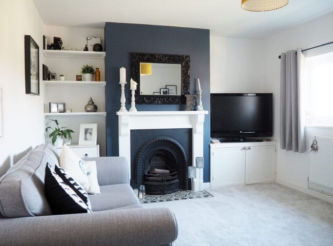 A modern scandi looking living room with grey sofa, curtains and carpet, deep blue chimney breast, cast iron fireplace and white fire surround