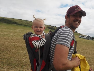 Daddy walking with daughter in baby carrier both smiling