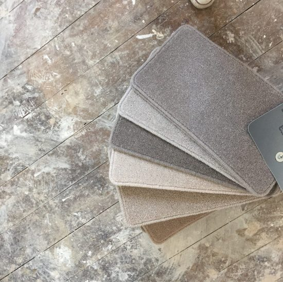 book of neutral carpet samples on wooden floor