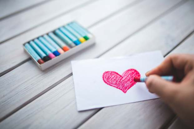 White paper with person drawing pink heart in crayon