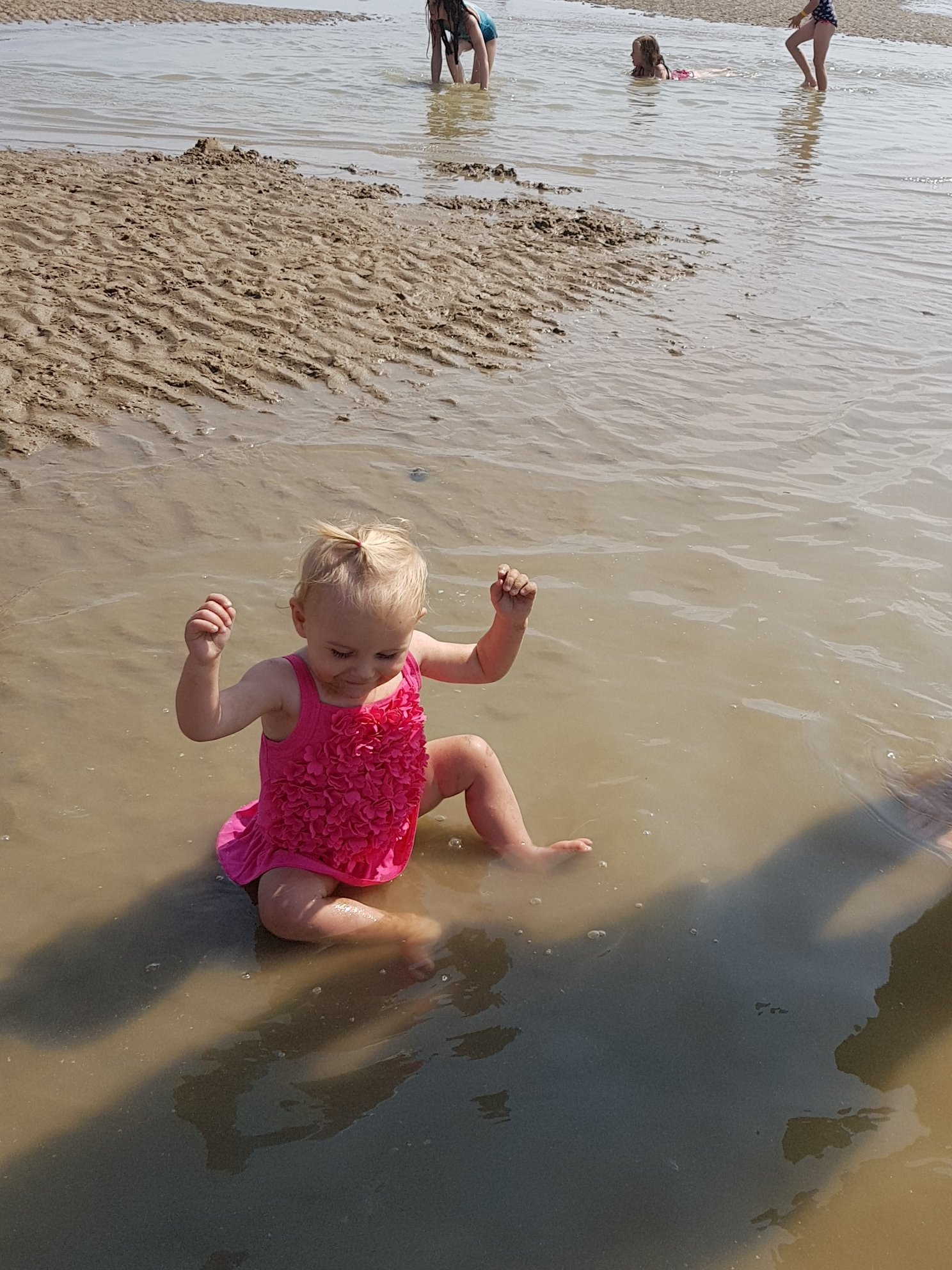 little girl playing in pool of water at seaside