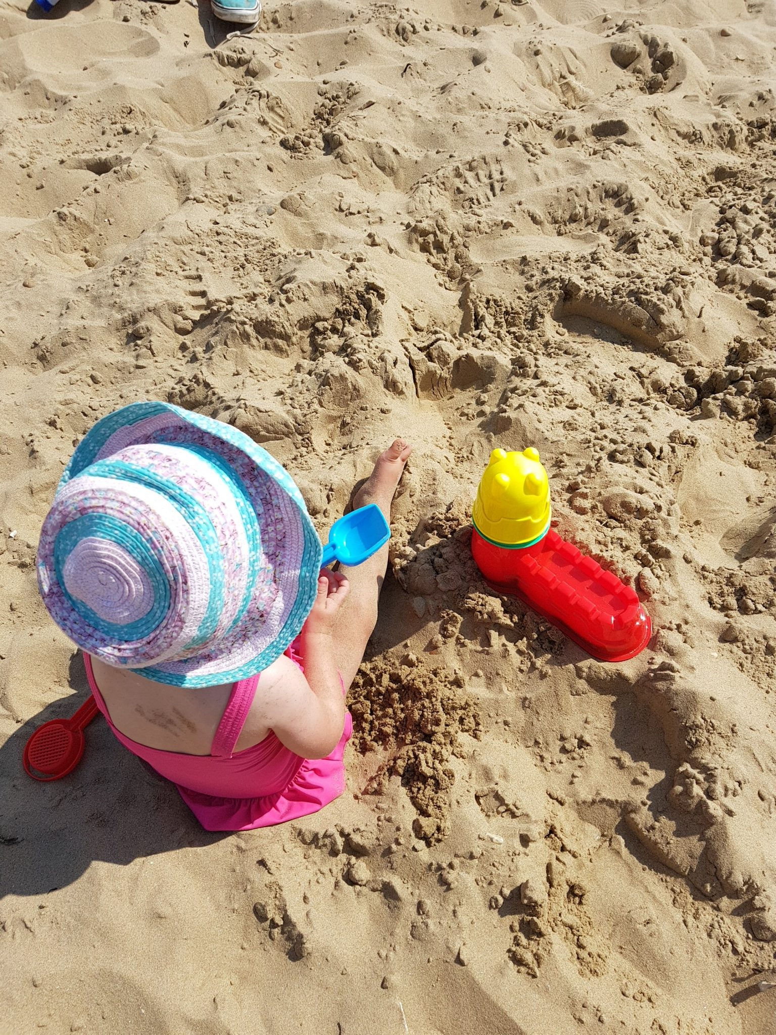 little girl playing in sand with pink sunhat