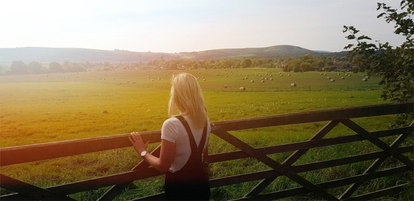 blonde haired woman looking out over field