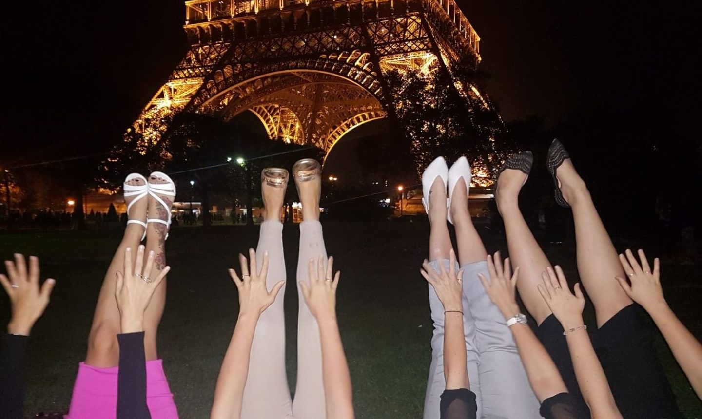 four girls legs and feet in front of eiffel tower