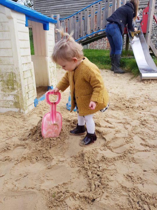 little girl in mustard coat digging in sandpit