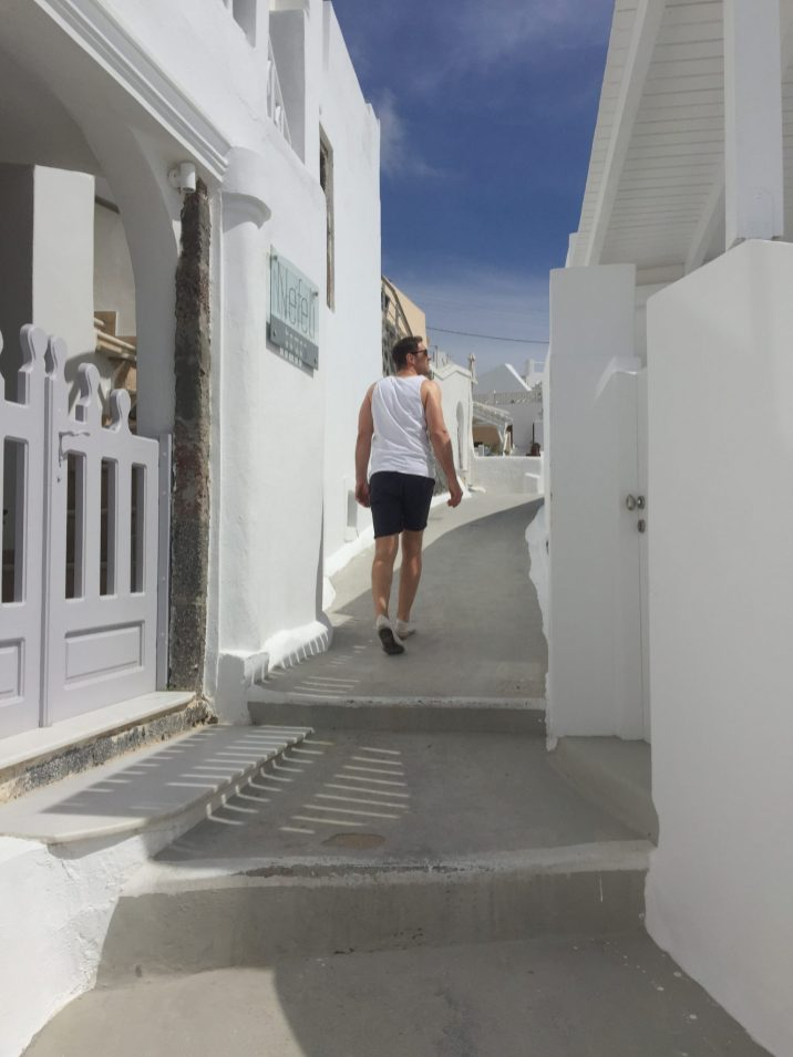 Man walking through white streets, Babymoon Guide to Santorini