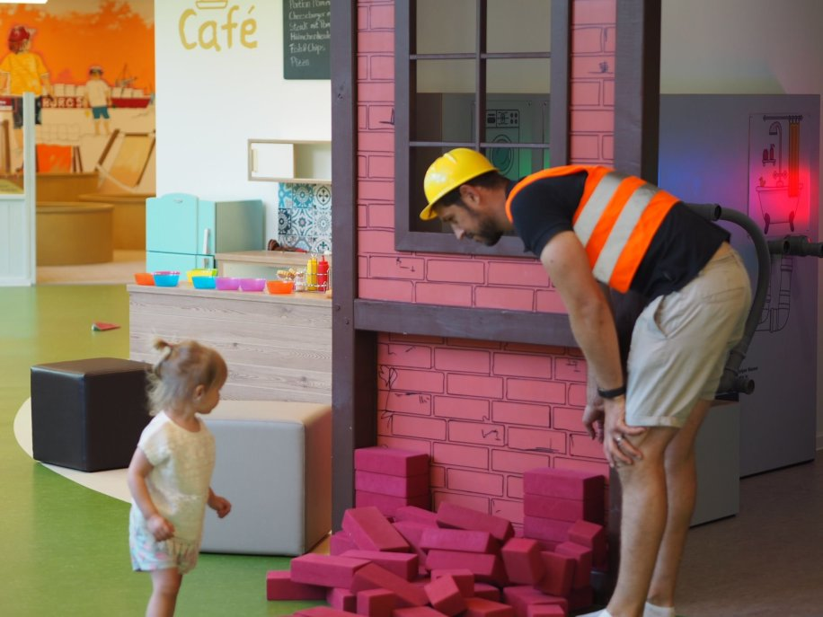 Daddy and daughter building a pretend brick wall, Hamburg with a Toddler   The Halcyon Years