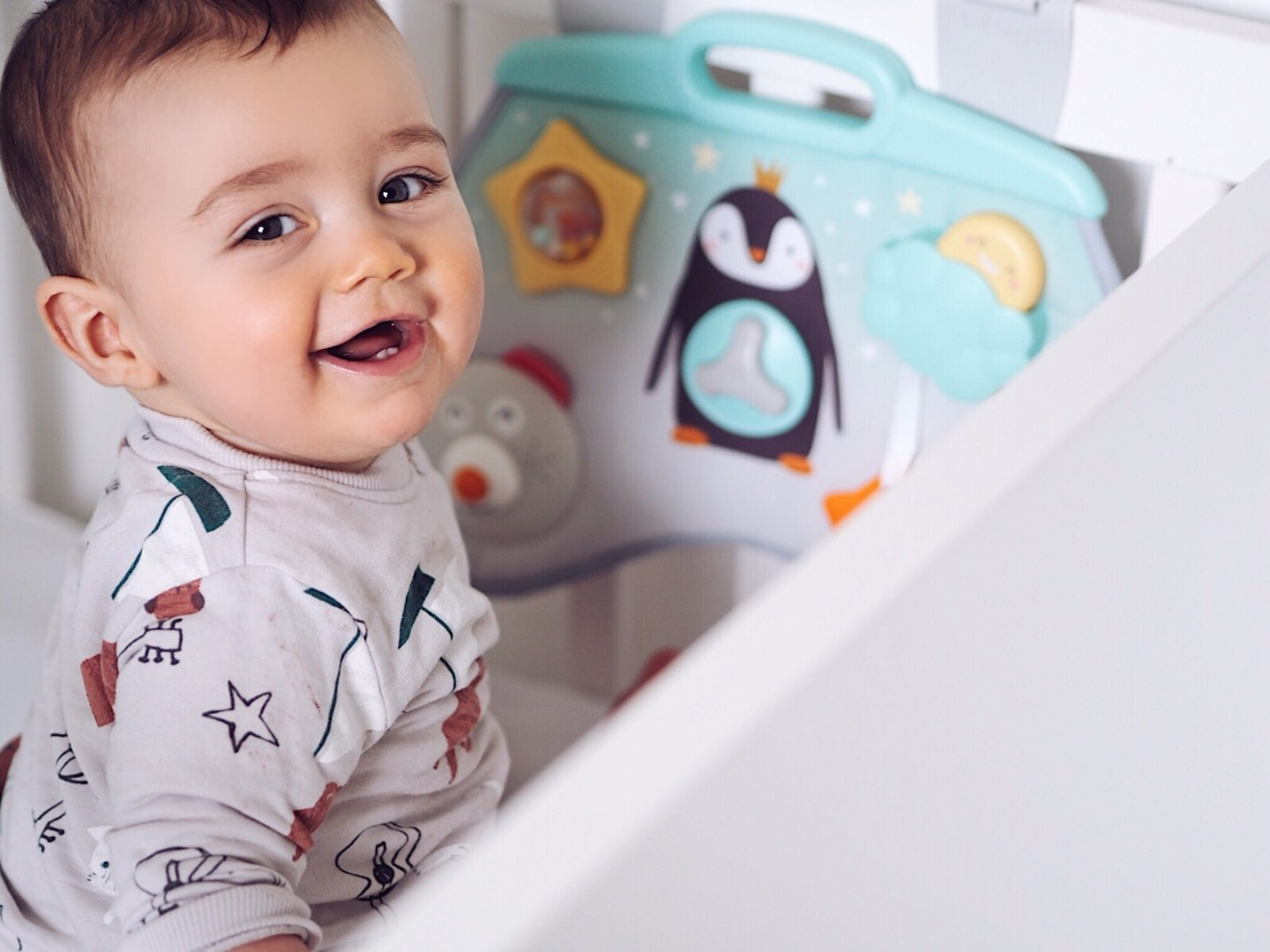 Taf Toys Laptoy Activity Centre review | The Halcyon Years (baby boy playing in a white cot with a grey flat toy attached to the side)