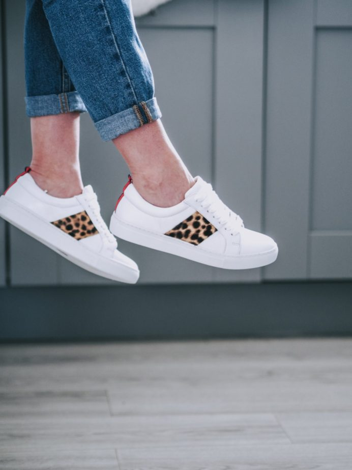 Boden staples for a capsule weekend wardrobe | The Halcyon Years [pair of ladies feet wearing white trainers with leopard print detail}