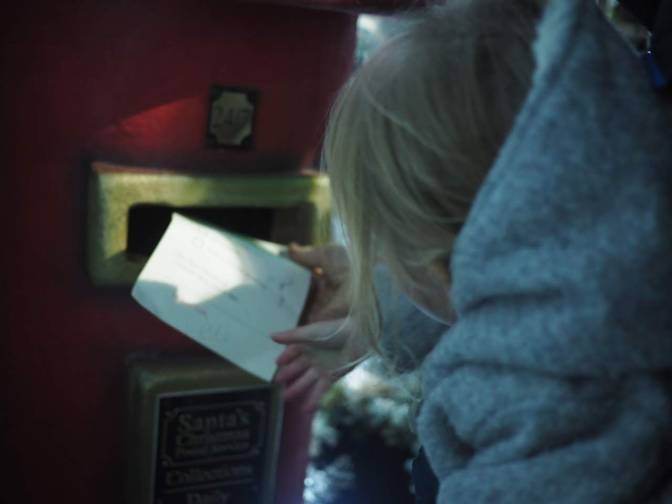 girl posting a letter to santa in a postbox at Tulleys Farm at Christmas