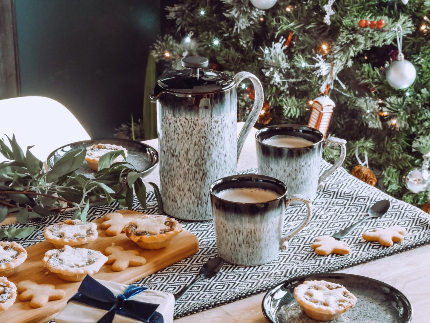 A grey Denby coffee pot and two mugs set out for Christmas with mince pies and a Christmas tree in the background