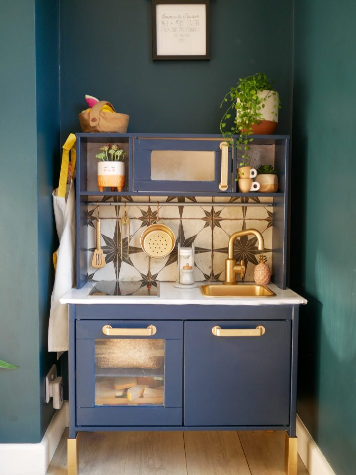 Ikea Duktig play kitchen revamped in navy blue with gold taps and black and white tiled splashback in a blue dining room
