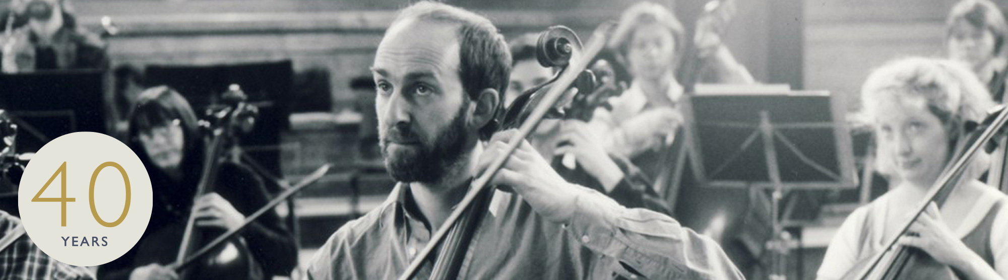 historical image of cellist in orchestra