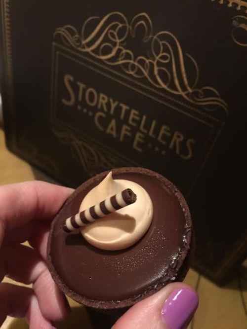 Salted caramel bite size dessert in front of Storytellers Cafe menu.