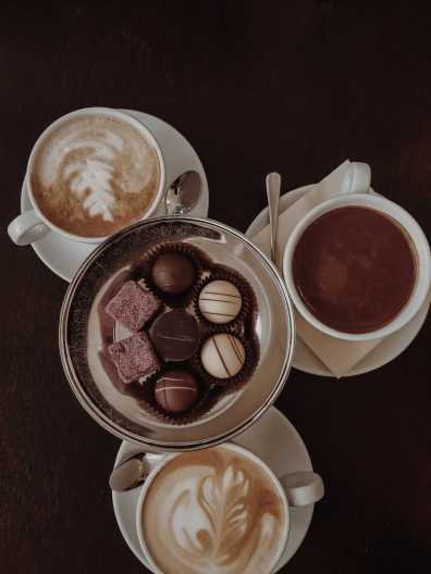 Breslau Sehenswürdigkeiten Pralinen auf Silbertablett und Cappuccino in Café
