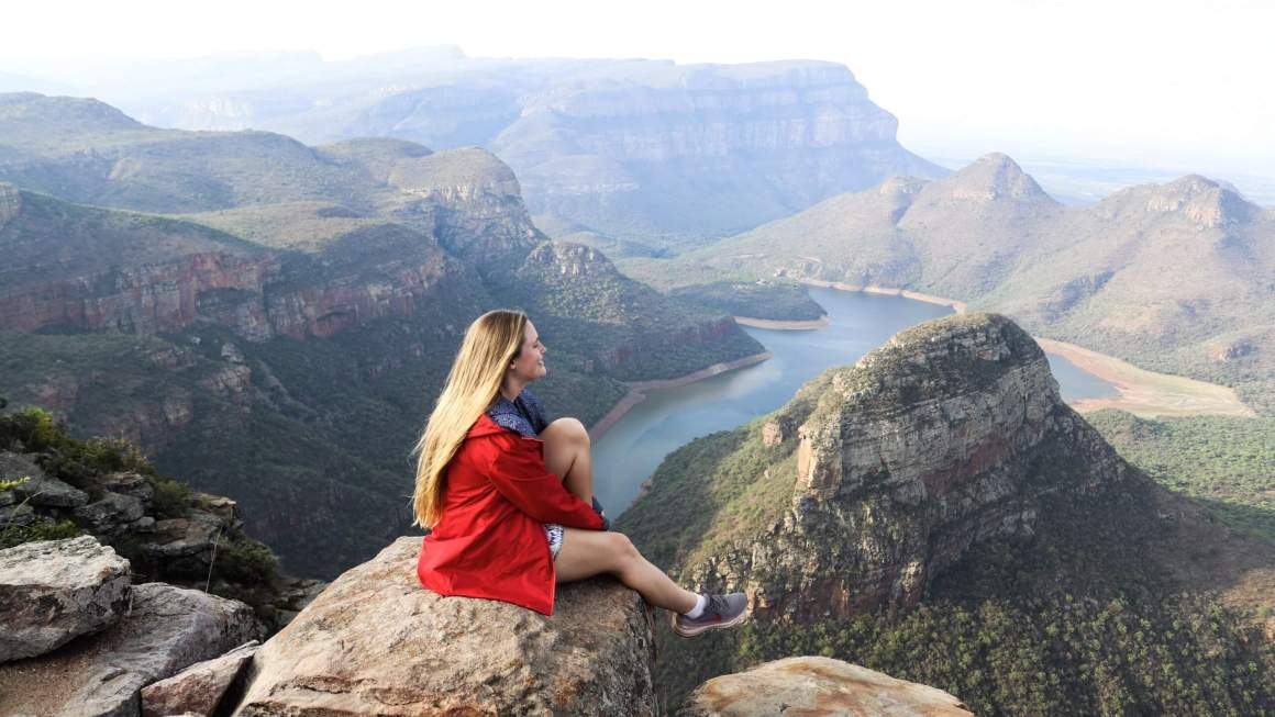 girl in red raincoat at blyde river canyon