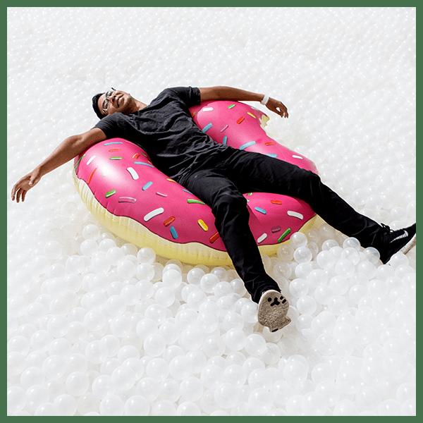 guy-sitting-in-donut-float-white-balls-chicago-January-events-thehauteseeker