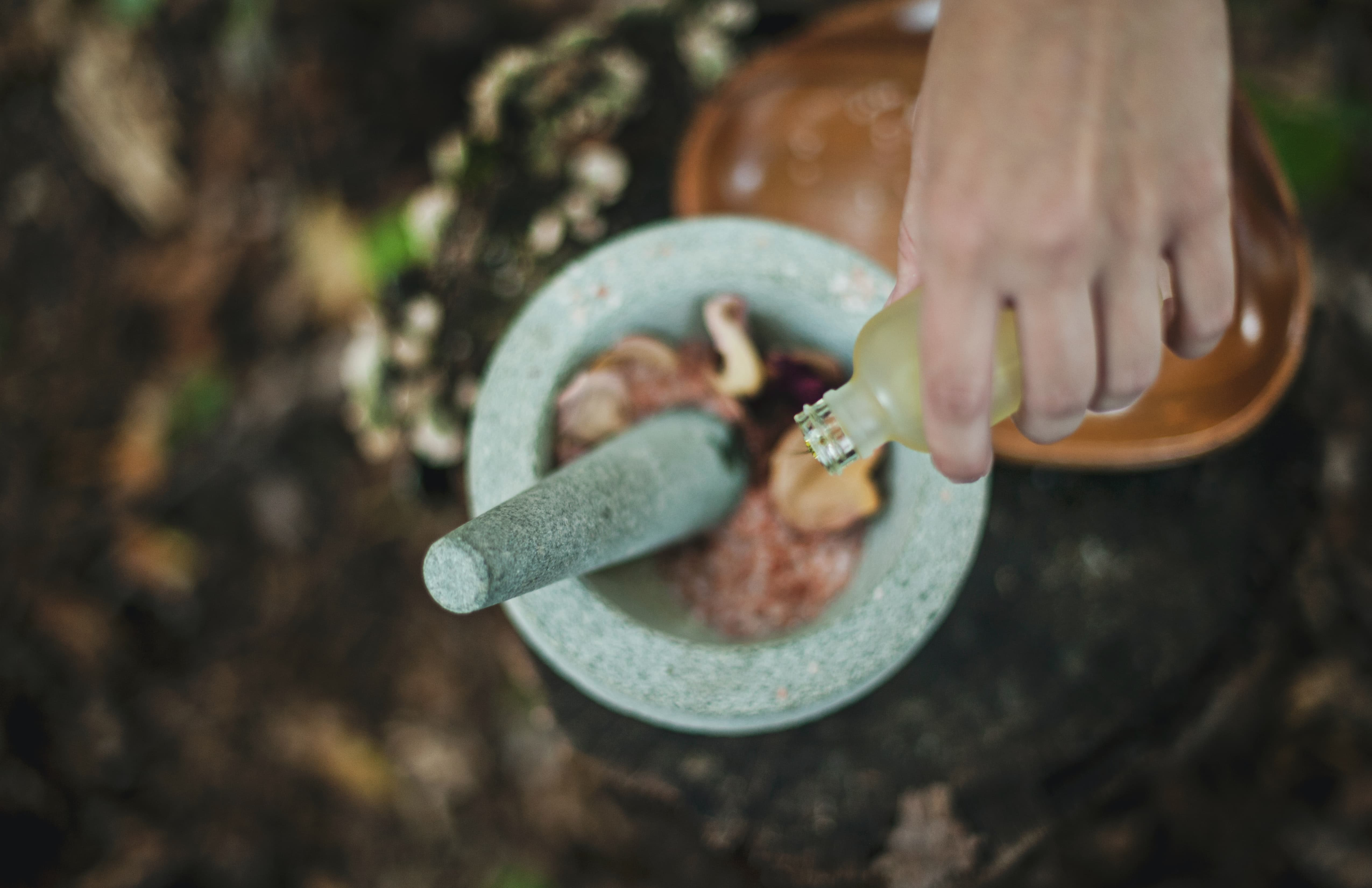 woman's hand pouring essential oils into a mortar and pestle filled with flowers