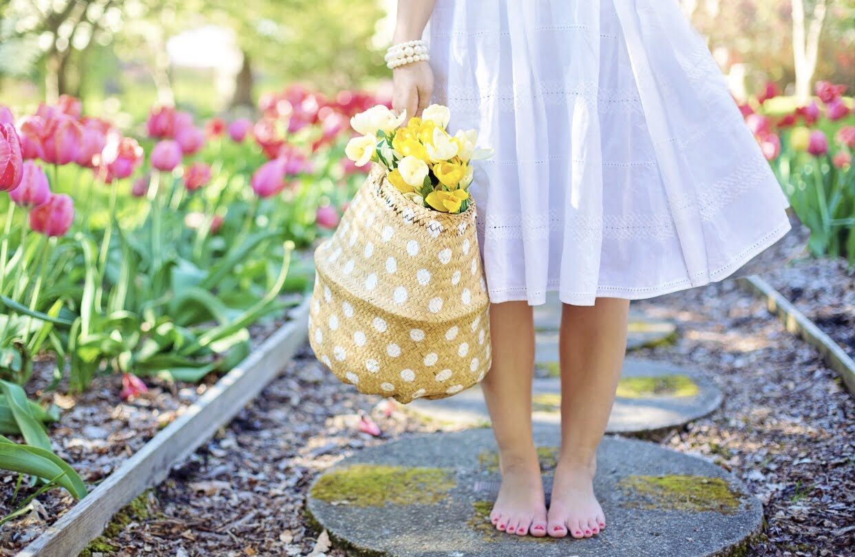 barefoot woman in white dress holding a basket of flowers