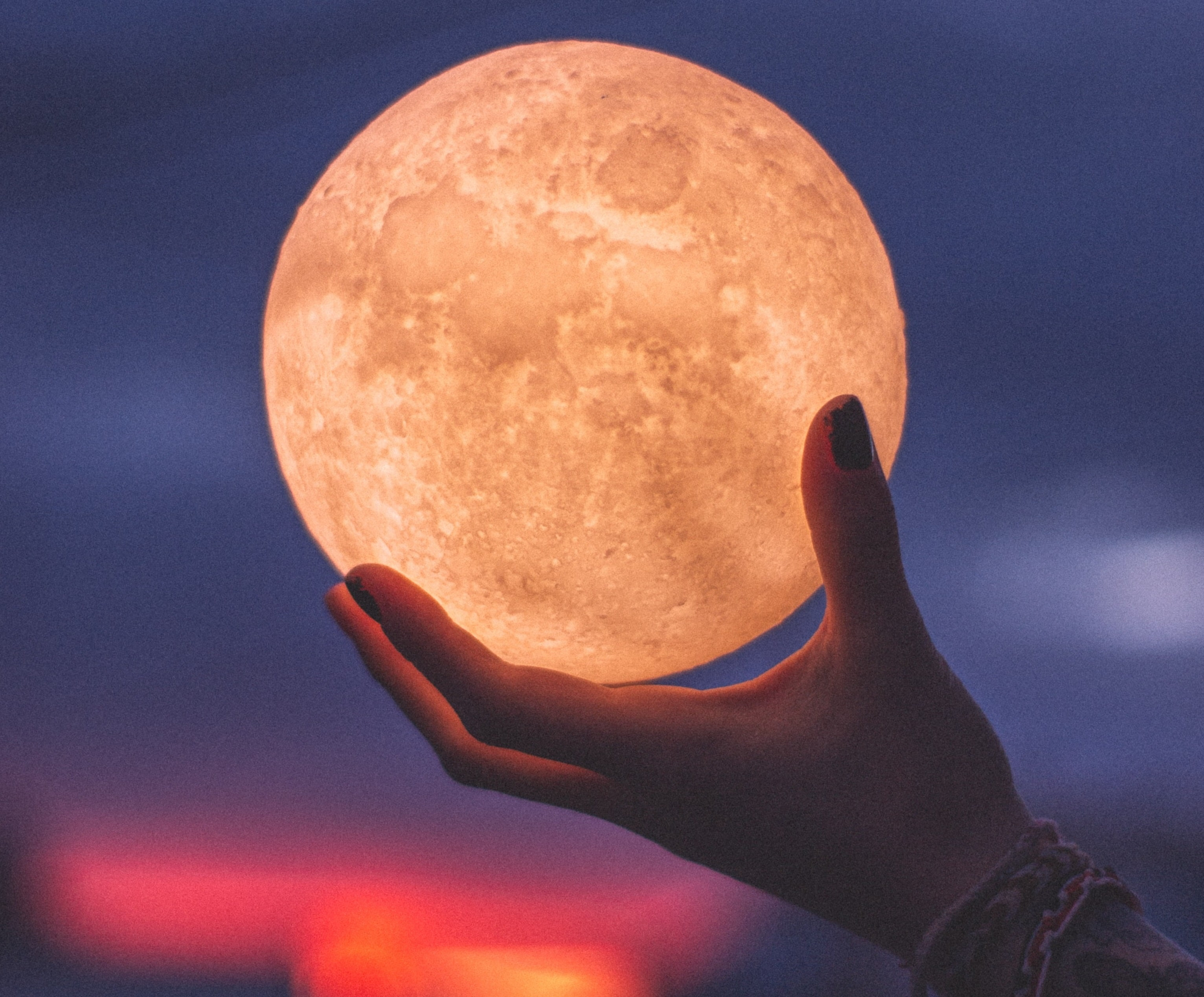 woman's hand holding a full moon nightlight