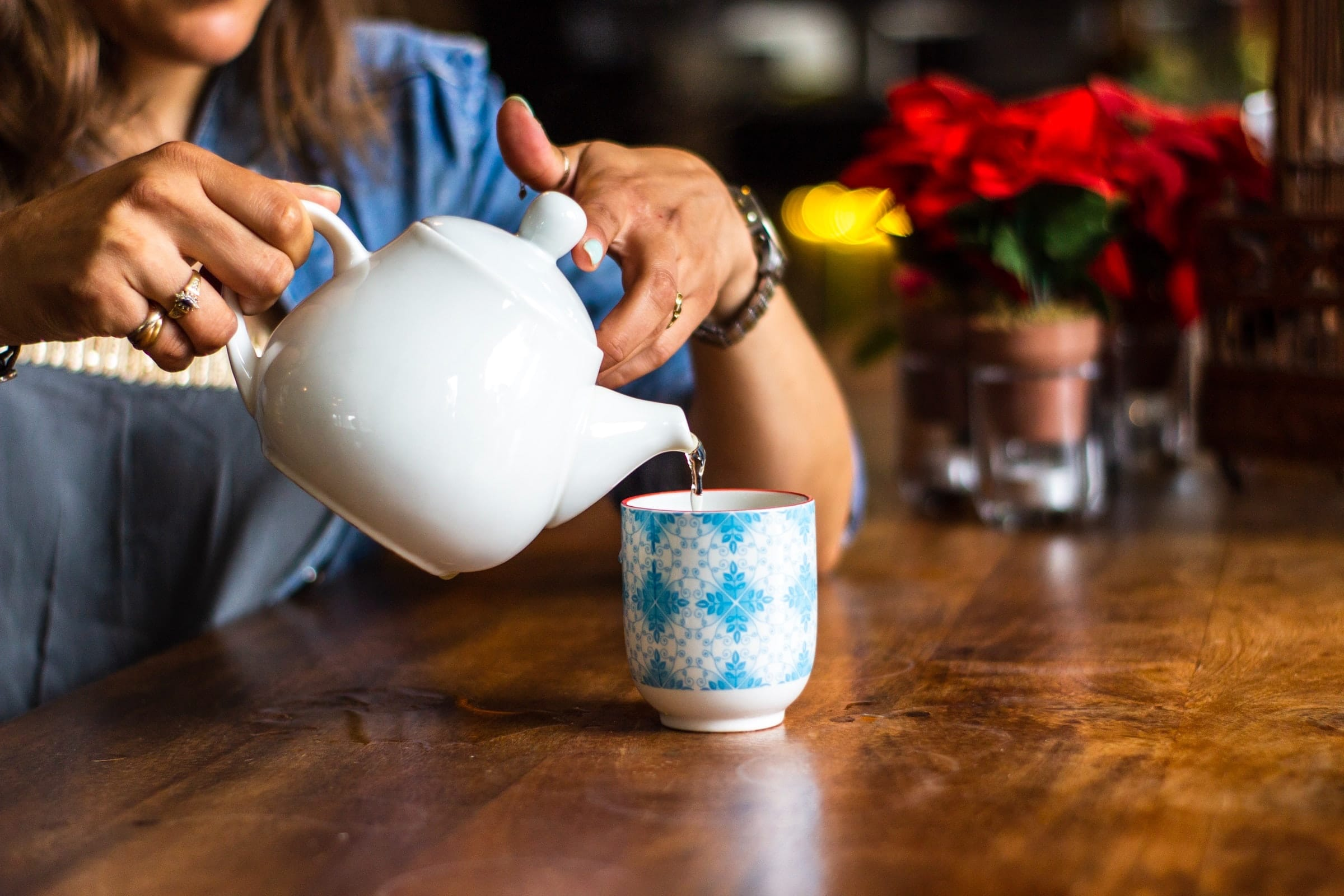 woman pouring moon water from a white tea pot into a blue and white mug