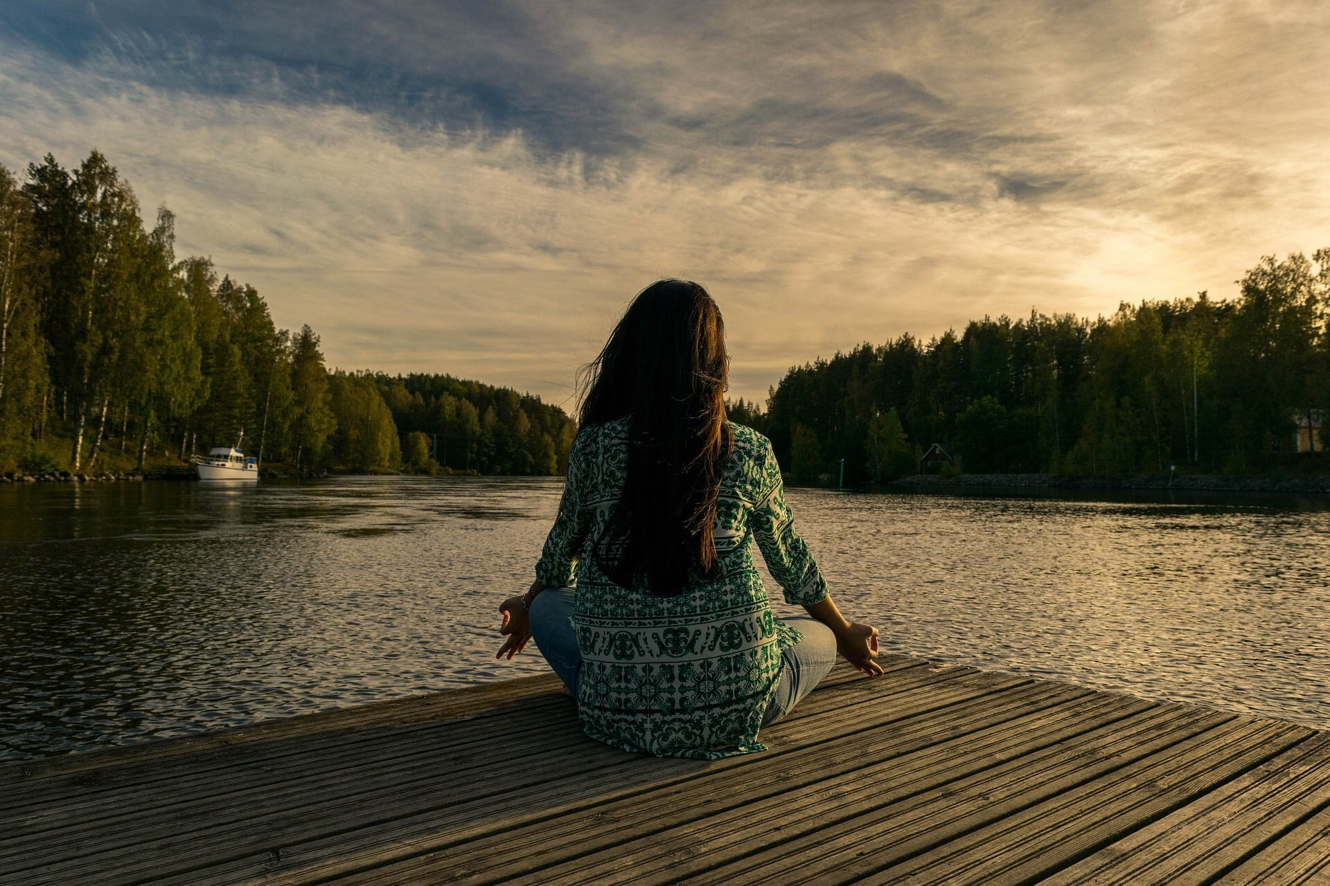 woman meditating on a dock at sunset