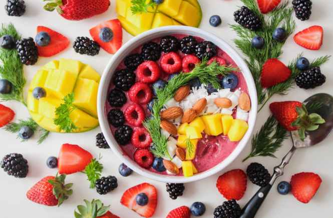 A smoothie bowl topped with fresh fruits and nuts for a healthy breakfast.