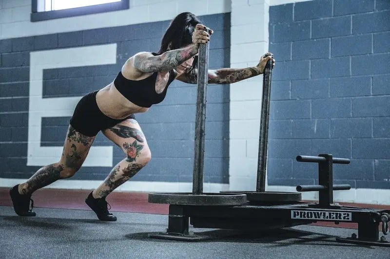 HIIT vs Crossfit woman pushing Prowler sled