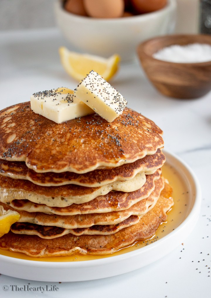 Stack of lemon pancakes with syrup, butter, and poppy seeds.