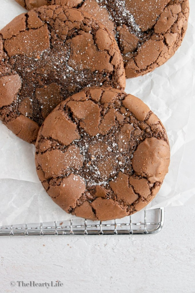 close shot of cookies on a cooling rack with sea salt sprinkled on top