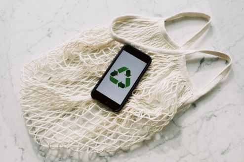 mobile phone with green recycling sign and mesh bag