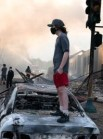 https://commons.wikimedia.org/wiki/File:A_man_stands_on_a_burned_out_car_on_Thursday_morning_as_fires_burn_behind_him_in_the_Lake_St_area_of_Minneapolis,_Minnesota_(49945886467).jpg