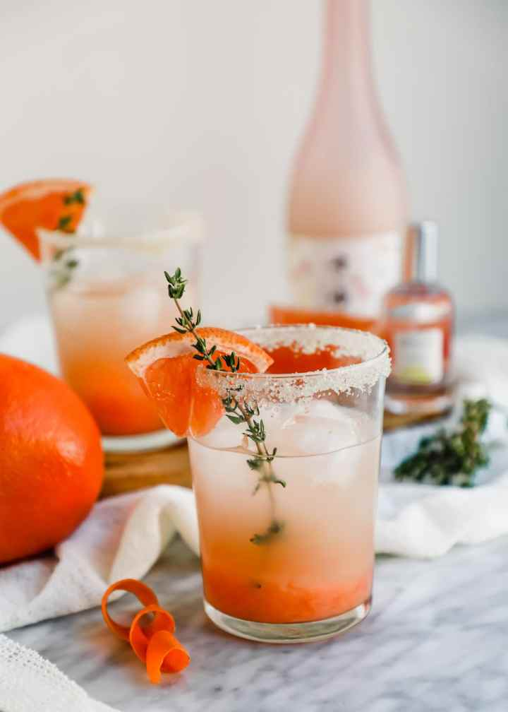 Grapefruit Honey Sake Cocktail with grapefruit slices and Skylar perfume.